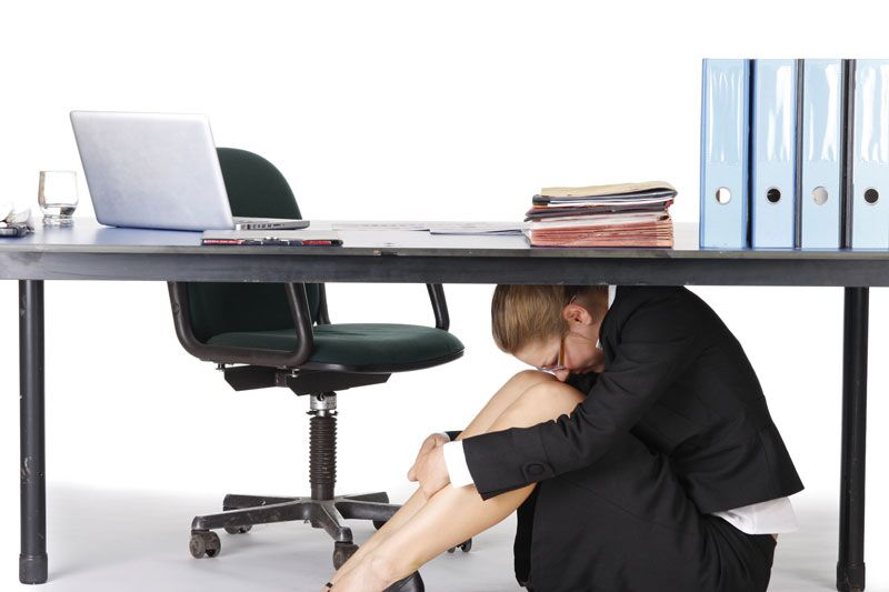 stressed woman hiding under desk