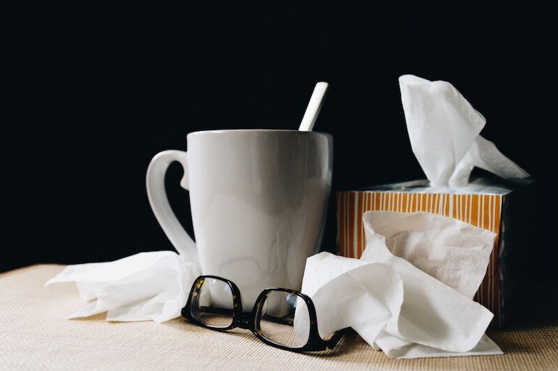 mug of tea next to crumpled tissues